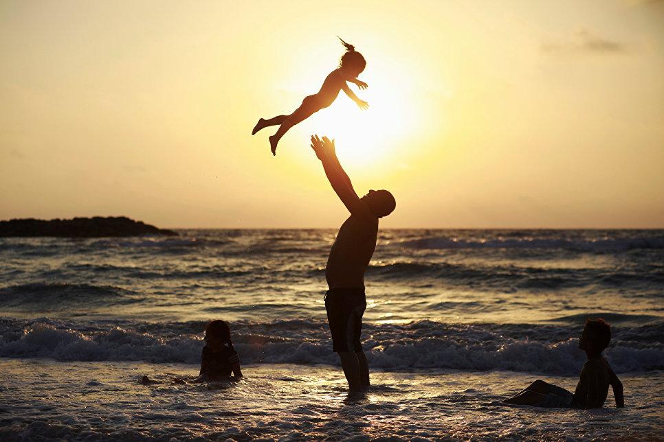 Мужчина играет с детьми на берегу Средиземного моря в Ашкелоне, Израиль