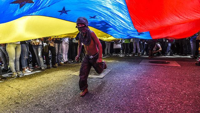 Мальчик пробегает под флагом Венесуэлы во время протестов в Каракасе