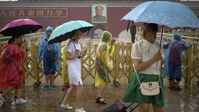 Прохожие во время сильного дождя на площади Тяньаньмэнь в Пекине, КНР. 6 июля 2016