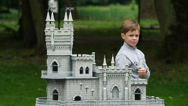 Посетитель рассматривает макет замка Ласточкино гнездо в Южном парке Калининграда