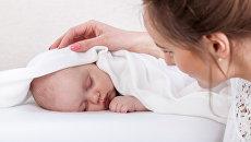 Взрослый рядом с спящим младенцем