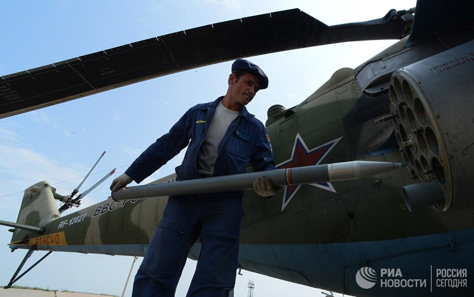 Авиационные техники готовят вертолет Ми-35 к вылету во время учений отдельного вертолетного полка на аэродроме Черниговка в Приморском крае