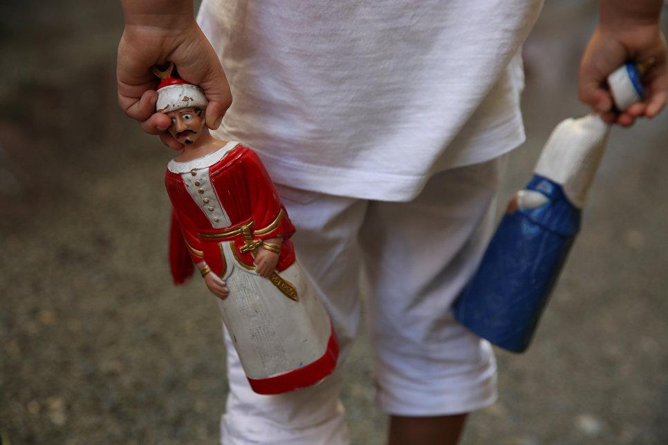 Мальчик держит статуэтки гигантов во время фестиваля Сен-Фермин в Памплоне