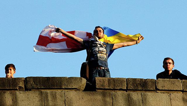 Человек держит флаги Грузии и Украины в Тбилиси