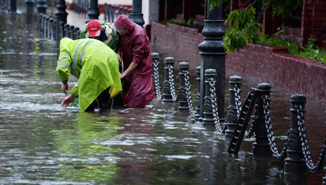 Работники коммунальной службы открывают решетки ливневой канализации на улице во Владивостоке. Архивное фото