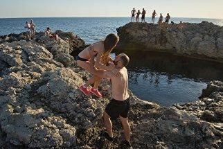 тдыхающие у природного бассейна Чаша любви на мысе Тарханкут в Крыму