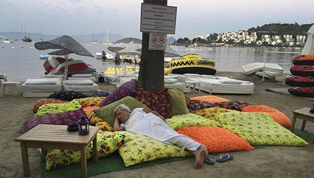 Мужчина спит в пляжной зоне после того как покинул отель во время землетрясения близ турецкого города Бодрум