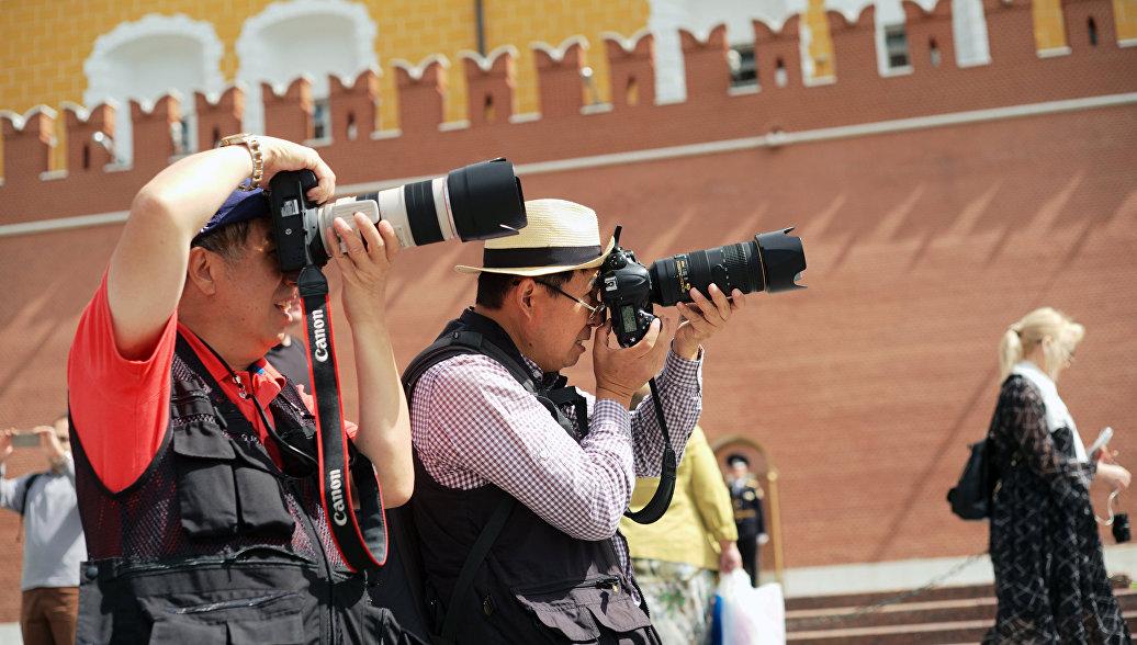 Туристы фотографируют в Александровском саду в Москве. 26 июля 2017
