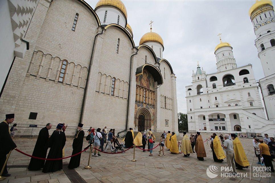 Туристы и священнослужители на Соборной площади Московского Кремля перед началом крестного хода в Москве к памятнику князя Владимира в День крещения Руси