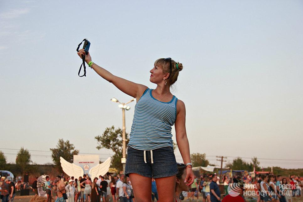 Девушка делает селфи на территории музыкального фестиваля ZBFest