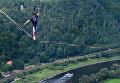 Слэклайнер проходит по стропе с завязанными глазами над рекой Эльбой в Крепости Кенигштайн, Германия