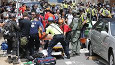 Спасатели помогают пострадавшим после того, как автомобиль врезался в группу противников акции ультраправых, которая проходит в городе Шарлоттсвилл в штате Виргиния