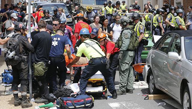 Спасатели помогают пострадавшим после того, как автомобиль врезался в группу противников акции ультраправых в Шарлоттсвилле