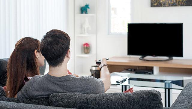 Молодая пара смотрит телевизор. Архивное фото