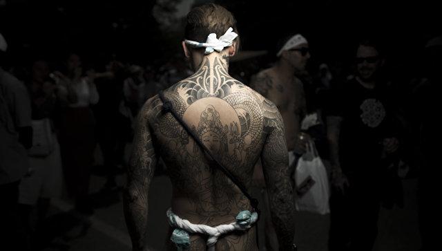 Мужчина с традиционной японской татуировкой Ирезуми на фестивале Сандзя-мацури в Токио