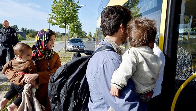 Семья мигрантов из Афганистана входит в автобус после прибытия на железнодорожную станцию Шенефельд, Германия