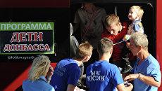 Сотрудники МЧС РФ помогают родителям с детьми из Донбасса, которые нуждаются в лечении, во время посадки на спецборт МЧС РФ в аэропорту Ростова-на-Дону перед отправкой в Москву. Архивное фото