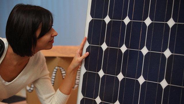 Девушка рассматривает солнечную панель. Архивное фото