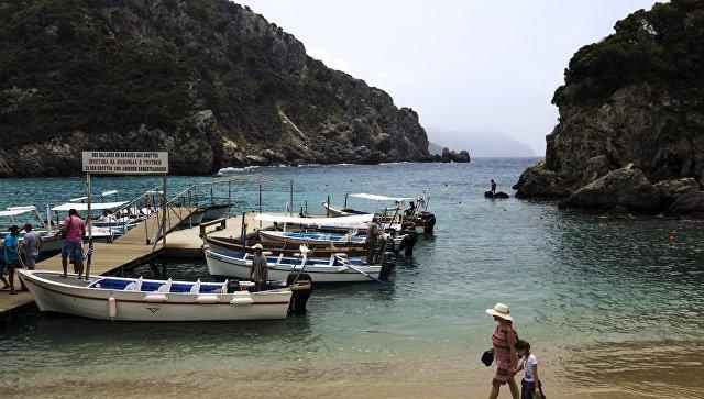 Туристы на пляже Адриатического моря в деревне Палеокастрица на греческом острове Корфу