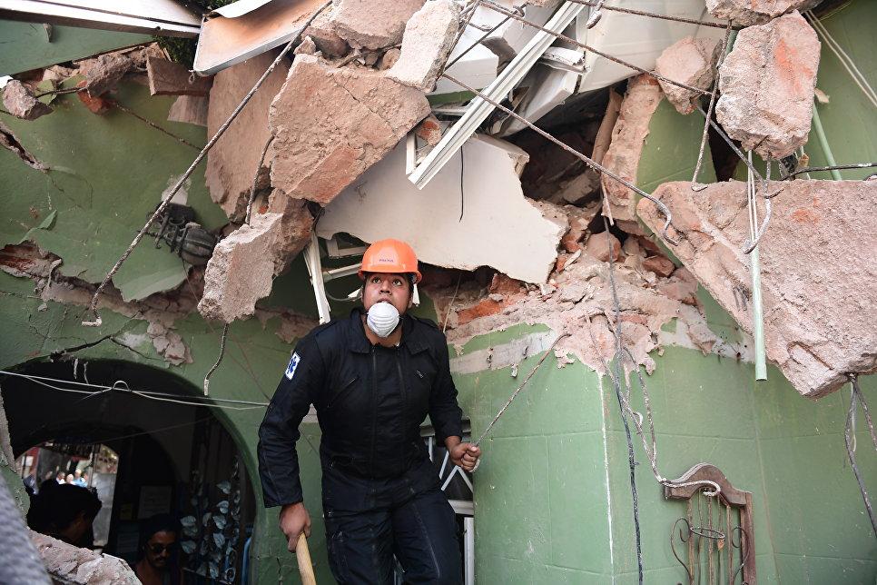 Спасатель ищет выживших после землетрясения в Мехико. 19 сентября 2017