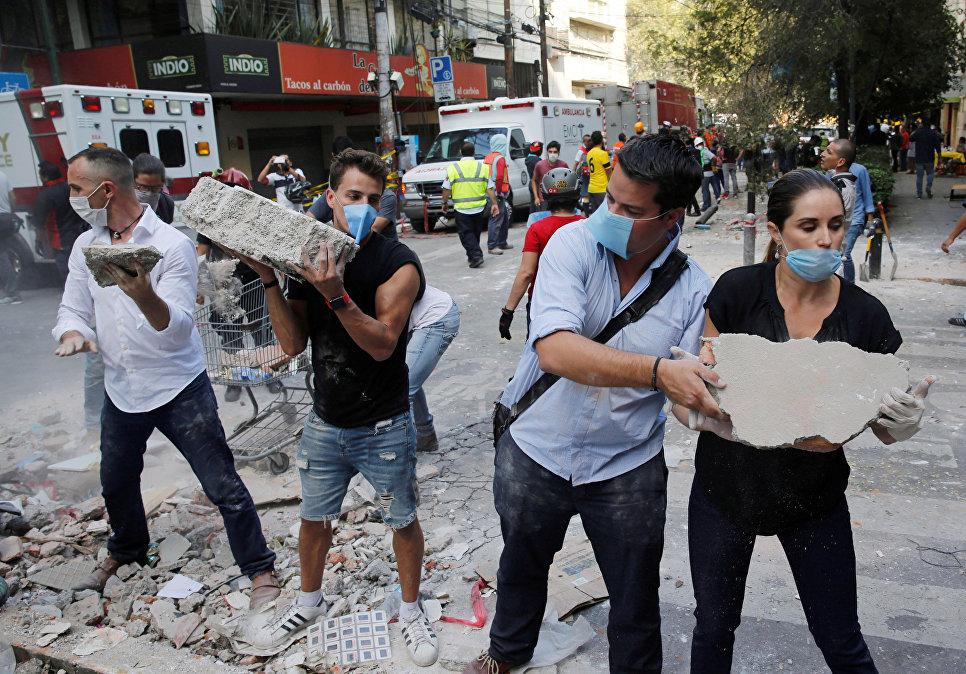 Люди помогают разгребать завали после землетрясения в Мехико. 19 сентября 2017