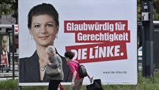 Женщины проходят мимо предвыборного плаката с кандидатом от Левой партии в Берлине