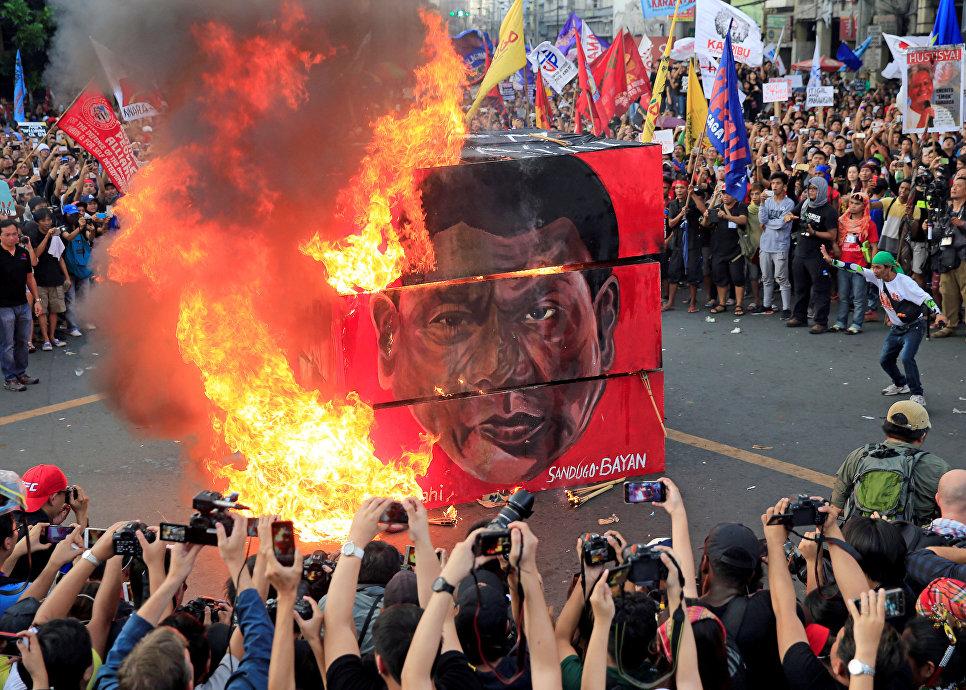 Протестующие сжигают портрет президента Филиппин Родриго Дутерте в Маниле