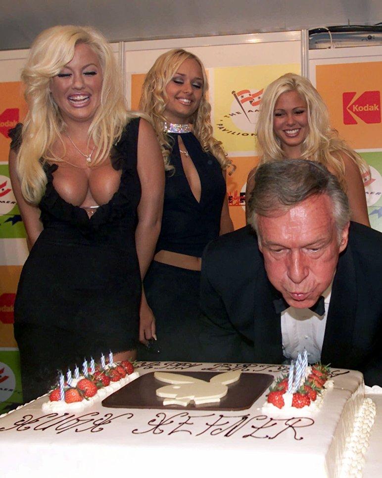 Основатель Playboy Хью Хефнер задувает свечи на свой 75-летний юбилей. 12 мая 2001