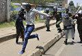 Демонстрант убегает от полиции во время акции протеста в Найроби, Кения.
