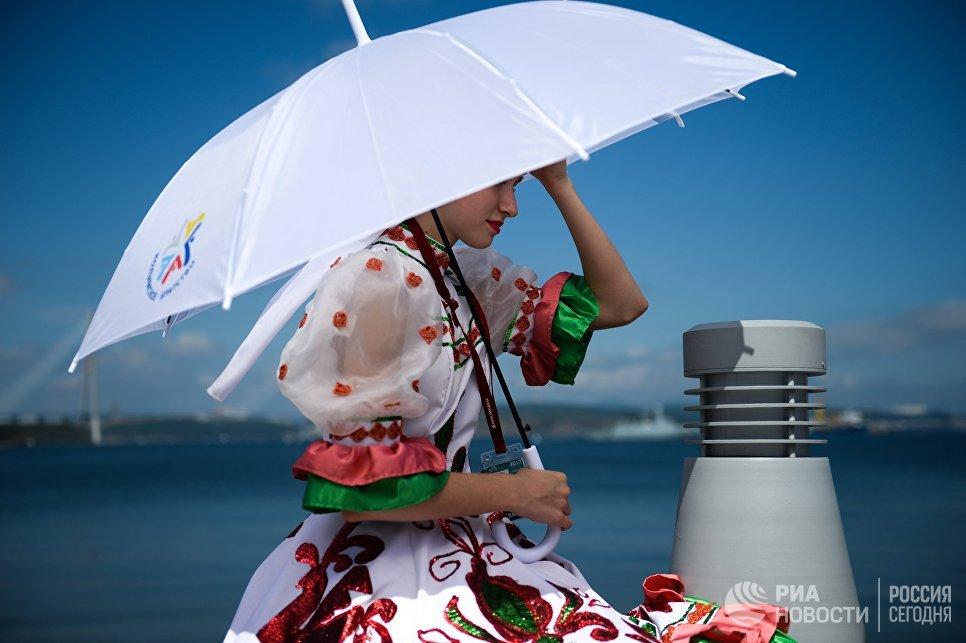 Девушка с зонтом на набережной бухты Аякс возле кампуса ДВФУ перед открытием выставки Улица Дальнего Востока в рамках ВЭФ во Владивостоке