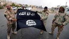 Бойцы сирийского отряда народного ополчения Соколы пустыни демонстрируют флаг Исламского государства (ИГ, запрещена в РФ). Архивное фото