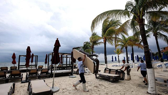 Служащий отеля собирает оборудование в предверии шторма Нэйт