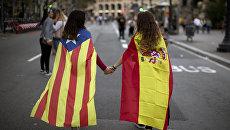 Девушки в флагах Испании и Каталонии во время демонстрации в Барселоне. 3 октября 2017