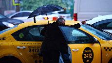 Мужчина у автомобиля такси в Москве во время дождя. Архивное фото