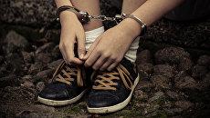 Подросток в наручниках. Архивное фото