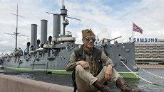 Мужчина на Петроградской набережной возле музея Крейсер Аврора в Санкт-Петербурге