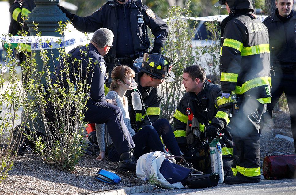 Спасатели оказывают помощь пострадавшей в результате наезда грузовика на велосипедистов в Нью-Йорке. 31 октября 2017