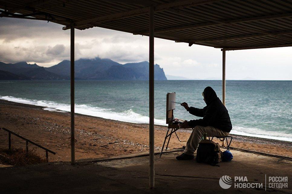 Художник рисует на одном из пляжей Севастополя