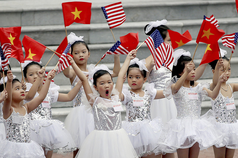 Дети машут флажками перед церемонией приветствия президента США Дональда Трампа в Президентском дворце в Ханое, Вьетнам