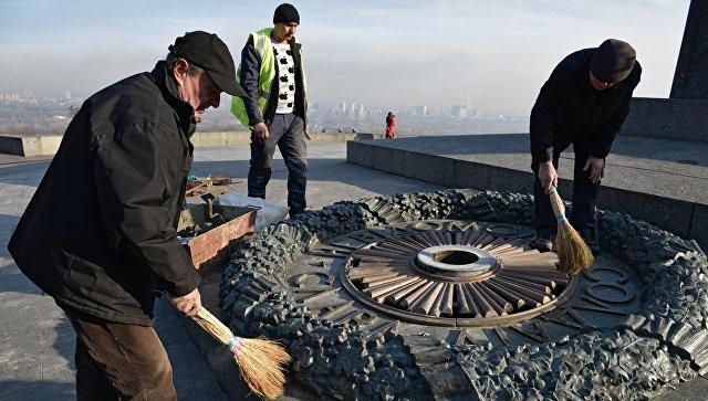 Работники Киевгаз очищают залитый цементом мемориал Вечный огонь. 20 ноября 2017