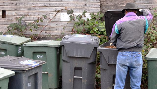Мужчина рядом с мусорными контейнерами. Архивное фото