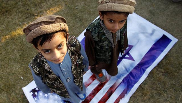 Дети стоят на флагах США и Израиля во время протеста против решения президента США Дональда Трампа признать Иерусалим столицей Израиля в Исламабаде, Пакистан. 7 декабря 2017