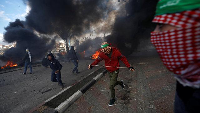 Палестинские протестующие во время столкновений с израильскими военными в районе города Рамалла на Западном берегу. 7 декабря 2017