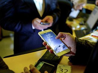 Посетитель московского магазина знакомится с функциями новых смартфонов Apple iPhone 6 и iPhone 6 plus
