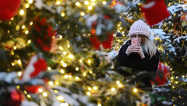 Девушка фотографируется у ели, оформленной для фестиваля Путешествие в Рождество. Архивное фото