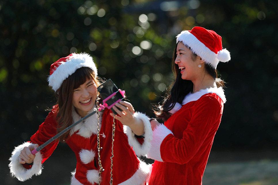 Девушки в костюмах Санта-Клаусов фотографируются во время благотворительного забега Tokyo Santa Run в Чибе