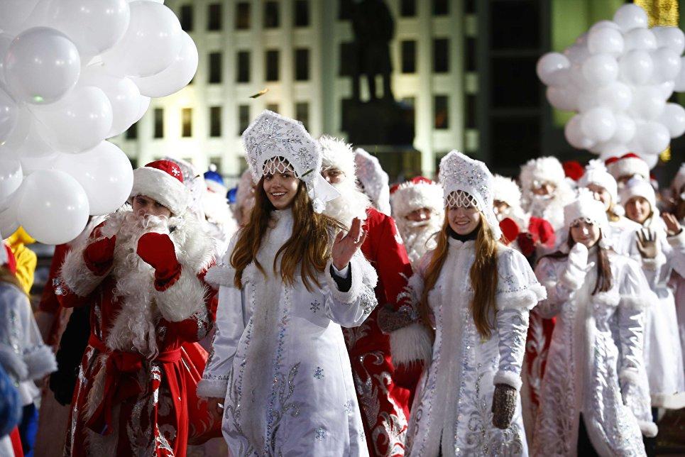 Люди в костюмах Снегурочек и Дед Морозов во время парада в Минске
