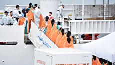Мигранты высаживаются с судна береговой охраны Италии после спасательной операции в море. 8 января 2018