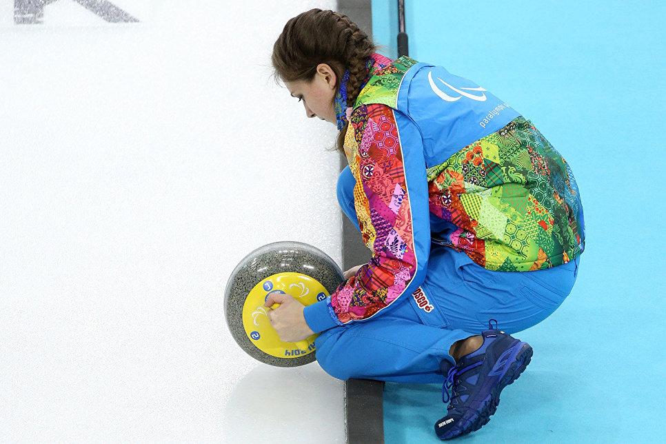 Волонтер зимних Паралимпийских игр в Сочи протирает камни для керлинга
