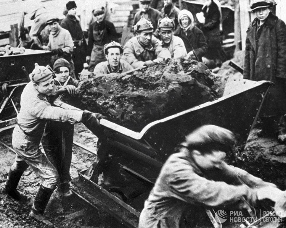 Красноармейцы и рабочие толкают вагонетки